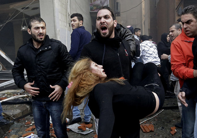 A Lebanese man carries an injured woman away from the site of a car bomb explosion in a Shiite area and stronghold of the Lebanese militant group Hezbollah at the southern suburb of Beirut, Thursday January 2, 2014. A large explosion has rocked a stronghold of the Shiite Hezbollah group in the southern suburbs of the Lebanese capital. (Photo by Hussein Malla/AP Photo)