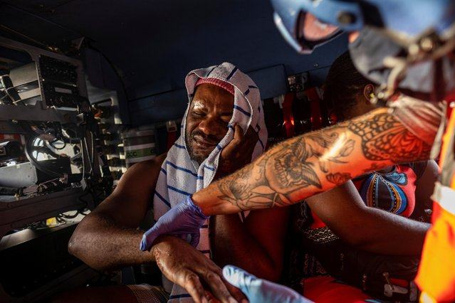 A U.S. Coast Guard flight crew member checks a patient during a medevac mission to Port-au-Prince of patients injured during the 7.2 magnitude quake, in Les Cayes, Haiti on August 21, 2021. (Photo by Ricardo Arduengo/Reuters)