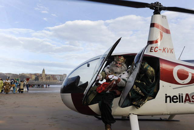 A man dressed as one of the Three Wise Men alights from a helicopter at San Lorenzo beach in Gijon January 5, 2014. Children in Spain traditionally receive their Christmas presents on the morning of January 6, delivered by the Three Wise Men. (Photo by Eloy Alonso/Reuters)