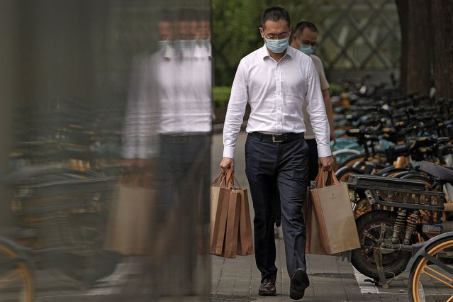 A man wearing a face mask to help protect from the coronavirus carries goody bags as he walks by a row of bicycles parked along a pavement in Beijing, Monday, September 13, 2021. (Photo by Andy Wong/AP Photo)