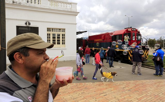 "A street vendor blows bubbles as a ""La Sabana"" tourist train makes a stop in Zipaquira city March 1, 2015. (Photo by Jose Miguel Gomez/Reuters)"