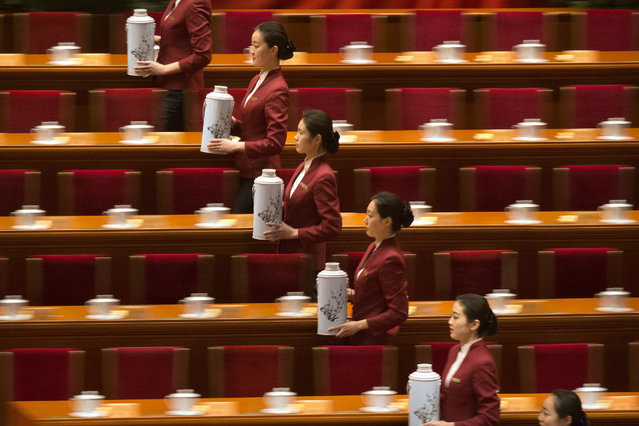 Attendants prepare to fill glasses for delegates before the opening session of the Chinese People's Political Consultative Conference at Beijing's Great Hall of the People, Thursday, March 3, 2016. The more than 2,000 members of China's top legislative advisory body convened their annual meeting Thursday, kicking off a political high season that will continue with the opening of the national congress on Saturday. (Photo by Mark Schiefelbein/AP Photo)