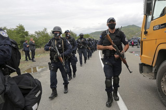 Kosovo police officers walk to replace their colleagues near the northern Kosovo border crossing of Jarinje on Tuesday, September 21, 2021. Tensions soared Monday when Kosovo special police with armored vehicles were sent to the border to impose a rule on temporarily replacing Serb license plates from cars while they drive in Kosovo. (Photo by Visar Kryeziu/AP Photo)