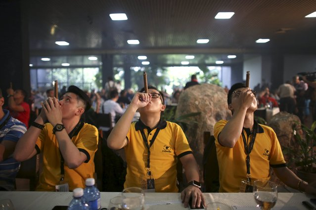 Competitors from China smoke as they compete for the longest ash during the XVIII Habanos Festival in Havana, March 3, 2016. (Photo by Alexandre Meneghini/Reuters)