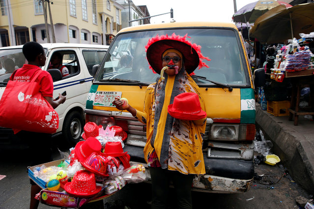 A woman sells Christmas items in front of a vehicle parked along a road in the central business district, near Marina in Lagos, Nigeria December 13, 2016. (Photo by Akintunde Akinleye/Reuters)