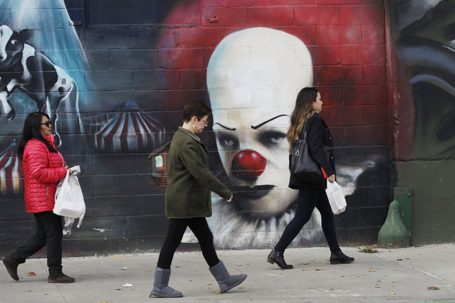 In this Wednesday, November 7, 2018, photo, people walk past a mural in Long Island City in the Queens borough of New York. Across the East River from midtown Manhattan, Long Island City is a longtime industrial and transportation hub that has become a fast-growing neighborhood of riverfront high-rises and redeveloped warehouses, with an enduring industrial foothold and burgeoning arts and tech scenes. (Photo by Mark Lennihan/AP Photo)