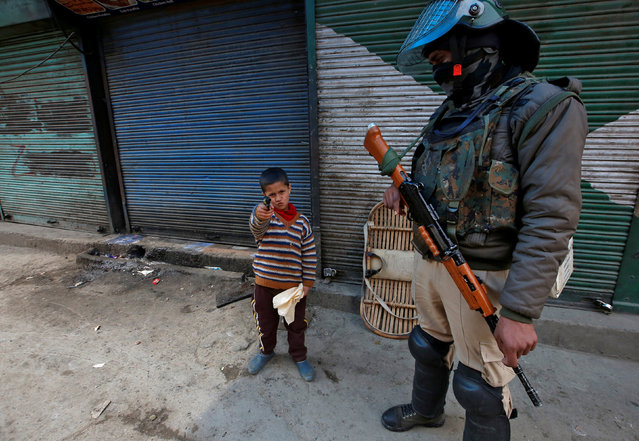 A boy plays with his toy pistol next to an Indian policeman standing guard in front of closed shops during a strike called by Kashmiri separatists against the arrest of Yasin Malik, Chairman of Jammu Kashmir Liberation Front (JKLF), a separatist party, in Srinagar March 8, 2019. (Photo by Danish Ismail/Reuters)
