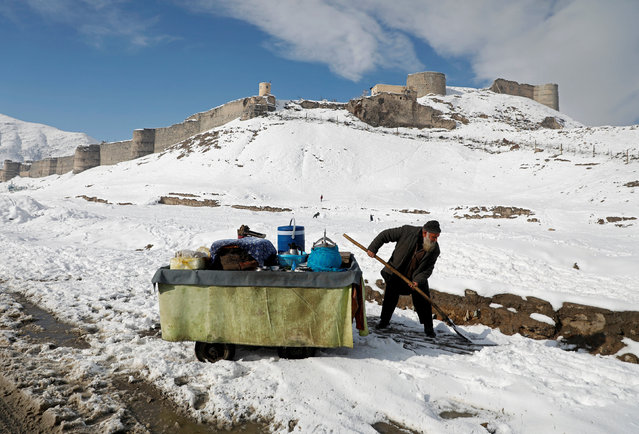 An Afghan man removes snow next to his handcart after the first snow in winter on the snow-covered ground in Kabul, Afghanistan, January 5, 2019. (Photo by Omar Sobhani/Reuters)