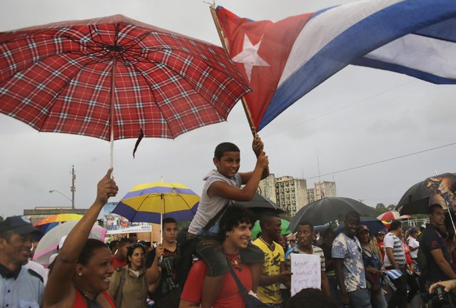 Cubans march under the rain for May Day at Revolution square in Havana, Cuba, Friday May 1, 2015. (Photo by Ramon Espinosa/AP Photo)