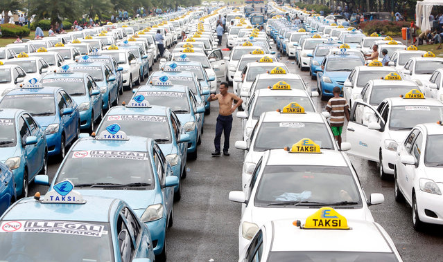 Taxi drivers stand beside their vehicles during mass stikes in Jakarta, Indonesia, 14 March 2016. More than a thousand  taxi and others public transportation drivers  in Jakarta held a mass strike against transportation-based online application including car-booking applications Uber and GrabTaxi. (Photo by Adi Weda/EPA)