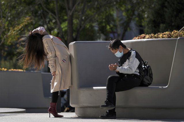 A woman wearing a face mask to help curb the spread of the coronavirus stretches her body next to a masked woman sitting on a bench outside a shopping mall in Beijing, Thursday, October 21, 2021. (Photo by Andy Wong/AP Photo)