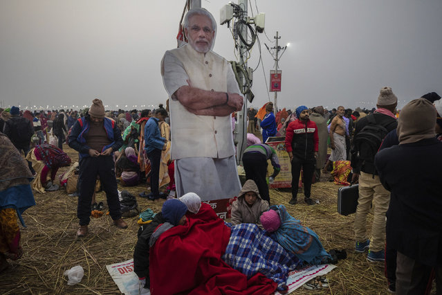 In this Monday, January 14, 2018 photo, people stand near a poster of Prime Minister Narendra Modi during the Kumbh Mela festival in Allahabad, India. The government spent unprecedented sums on the heavily-attended Hindu Kumbh Mela festival, with Modi and the chief minister, Yogi Adityanath, himself a Hindu monk, appearing in countless posters. (Photo by Bernat Armangue/AP Photo)
