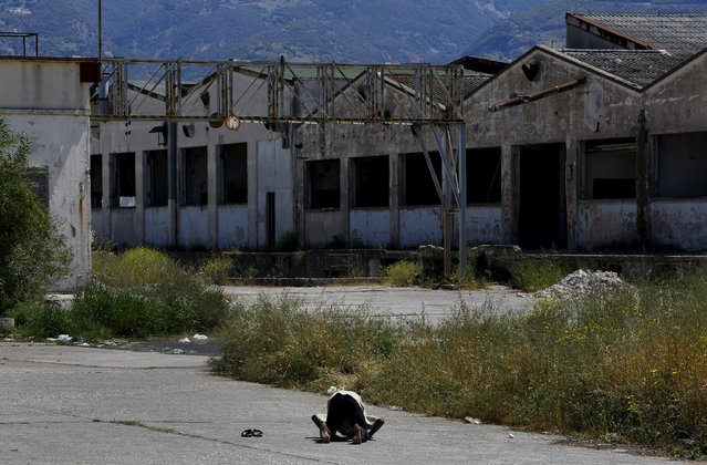 A Sudanese immigrant prays at an abandoned factory in the western Greek town of Patras May 4, 2015. (Photo by Yannis Behrakis/Reuters)