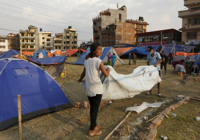 People displaced by the April 25 earthquake pack up their tent in Kathmandu, Nepal, May 6, 2015. (Photo by Olivia Harris/Reuters)