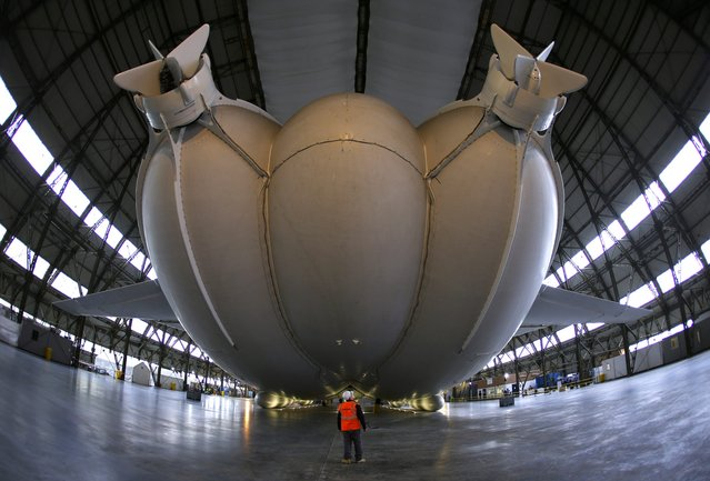 A worker stands under the Airlander 10 hybrid airship during its unveiling in Cardington, Britain March 21, 2016. The world's largest aircraft has been unveiled for the first time since being fully assembled in the UK. The 302ft (92m) long Airlander 10 – part plane, part airship – was floated in a First World War hangar in Bedfordshire. (Photo by Darren Staples/Reuters)