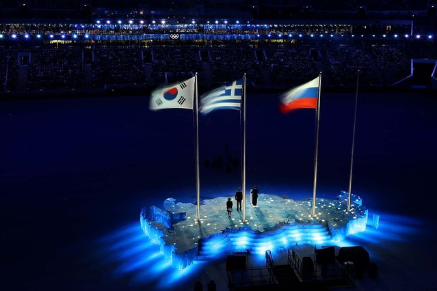 The South Korean, Greek and Russian Flags wave during the ceremony. (Photo by Joe Scarnici/Getty Images)