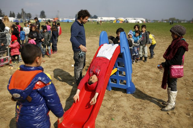 Children play on a slide at a makeshift camp for migrants and refugees at the Greek-Macedonian border near the village of Idomeni, Greece, March 28, 2016. (Photo by Marko Djurica/Reuters)