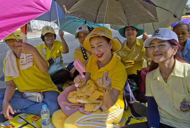 Thai people sit on a side-road, anticipating access to Suddhaisavarya Prasad Hall, in which Thailand's King Maha Vajiralongkorn scheduled to grant a public audience in Bangkok, Thailand, Monday, May 6, 2019. King Maha Vajiralongkorn was officially crowned amid the splendor of the country's Grand Palace, taking the central role in an elaborate centuries-old royal ceremony that was last held almost seven decades ago. (Photo by Gemunu Amarasinghe/AP Photo)