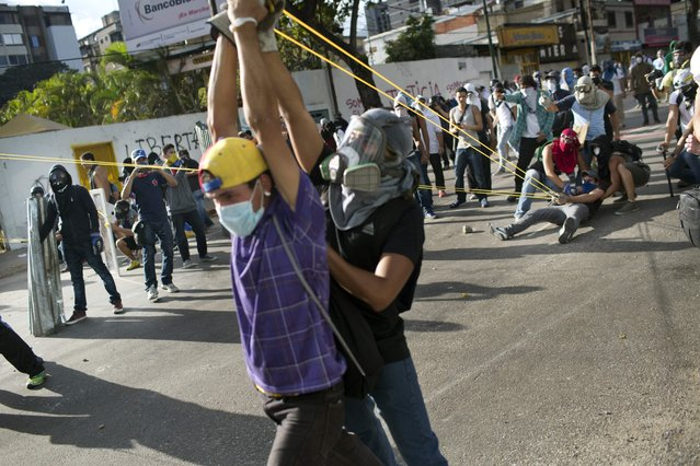 Demonstrators use a giant slingshot to launch stones at Bolivarian National Guardsduring anti-government protests in Caracas, Venezuela, Sunday, March 2, 2014. Since mid-February, anti-government activists have been protesting high inflation, shortages of food stuffs and medicine, and violent crime in a nation with the world's largest proven oil reserves. (Photo by Rodrigo Abd/AP Photo)