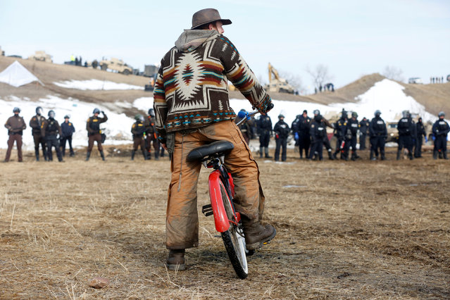 Jasper Spillman, 30, of Lawrence, Kansas, watches law enforcement officers advance into the main opposition camp against the Dakota Access oil pipeline near Cannon Ball, North Dakota, U.S., February 23, 2017. (Photo by Terray Sylvester/Reuters)