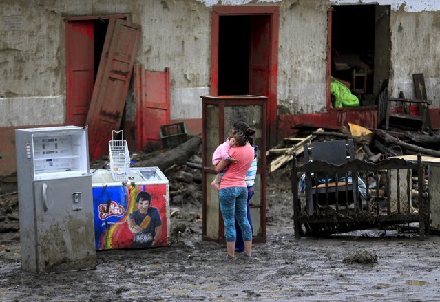 A woman with her baby stands in front of a damaged house after a landslide sent mud and water crashing onto homes close to the municipality of Salgar in Antioquia department, Colombia May 19, 2015. (Photo by Jose Miguel Gomez/Reuters)
