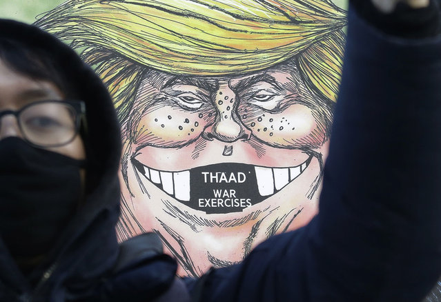 A South Korean protester stands in front of a cartoon depicting U.S. President Donald Trump during a rally against U.S. Defense Secretary Jim Mattis' visit, in front of the government complex in Seoul, South Korea, February 2, 2017. (Photo by Ahn Young-joon/AP Photo)