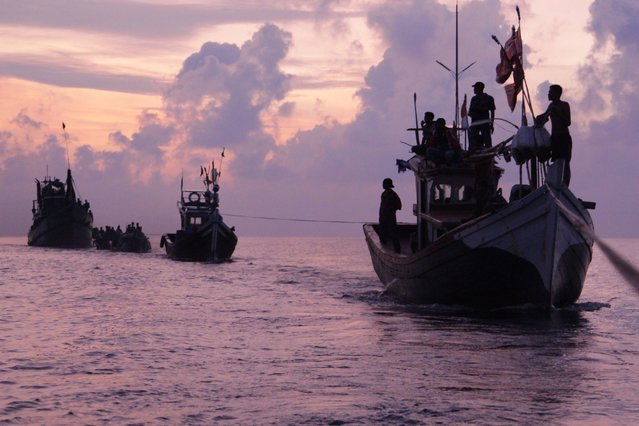 Acehnese fishermen are silhouetted by the rising sun as they rescue migrants who are stranded on their boat on the sea off East Aceh, Indonesia, Wednesday, May 20, 2015. Hundreds of migrants stranded at sea for months were rescued and taken to Indonesia, officials said Wednesday, the latest in a stream of Rohingya and Bangladeshi migrants to reach shore in a growing crisis confronting Southeast Asia. (Photo by S. Yulinnas/AP Photo)