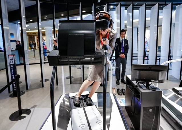"""A woman tests the Ski Rodeo game at the new Bandai Namco """"VR Zone: Project I Can"""" experience center in a shopping mall in Tokyo, Japan, 11 April 2016. The virtual reality center will allow people to try out six different VR reality simulation games in which Bandai Namco will receive valuable feedback on how to improve their virtual reality simulation technology. The center opens to the general public for a limited time from 15 April. (Photo by Christopher Jue/EPA)"""