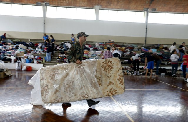 A soldier carries a mattress at a temporary shelter in a public gym in Dolores, the day after the city was hit by a tornado, April 16, 2016. (Photo by Andres Stapff/Reuters)