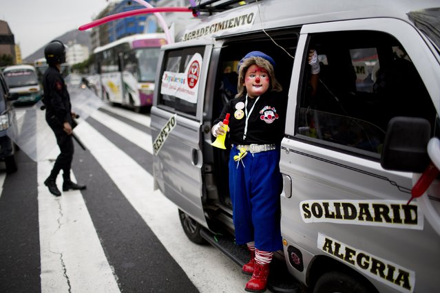 A clown standing on the doorway of a van accompanies the Peruvian Clown Day march in Lima Peru, Monday, May 25, 2015. (Photo by Rodrigo Abd/AP Photo)