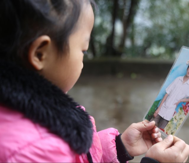 5-year-old Chinese girl Wang Anna weeps as she looks at a photo of her father at home in Zhuyuan village, Guizhou province, China on March 3, 2017. (Photo by Imaginechina/Rex Features/Shutterstock)