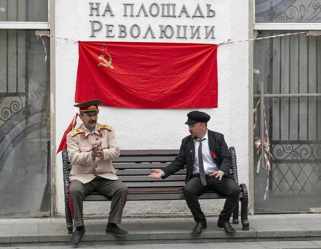 """Two men who impersonate Soviet founder Vladimir Lenin, right, and Soviet leader Joseph Stalin talk to each other waiting to pose with tourists in Moscow, Russia, Saturday, July 6, 2019. The words on the background is the name of the underground Station and reading """"Revolution Square"""". (Photo by Alexander Zemlianichenko/AP Photo)"""