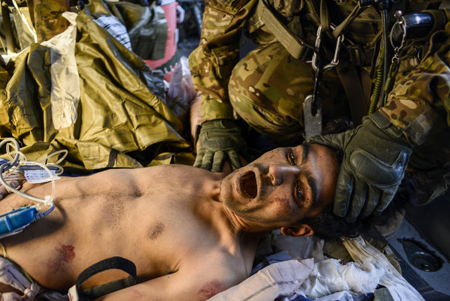 An Afghan soldier who'd just lost both legs due to an IED, is restrained by Sgt. James Bell, a crew chief, as the patient was very restless during the medevac flight, October 22, 2013. During medevac missions even crew chiefs are utilized as space is tight and the more hands available for care the better. (Photo by Air Force Tech. Sgt. Joshua L. DeMotts/USAF)