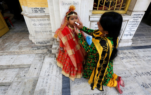 The mother of young girls dressed as Kumari applies lip gloss on her daughter before the start of the rituals to commemorate Navratri festival at Adyapith temple on the outskirts of Kolkata, India, April 15, 2016. (Photo by Rupak De Chowdhuri/Reuters)