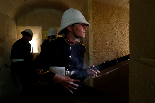 A National Heritage Trust historical re-enactor looks out of a gun port after firing his rifle during a re-enactment of Victorian-era British Army garrison life at the Fort Rinella coastal battery, built in 1878, in Kalkara, outside Valletta, Malta, April 27, 2016. (Photo by Darrin Zammit Lupi/Reuters)