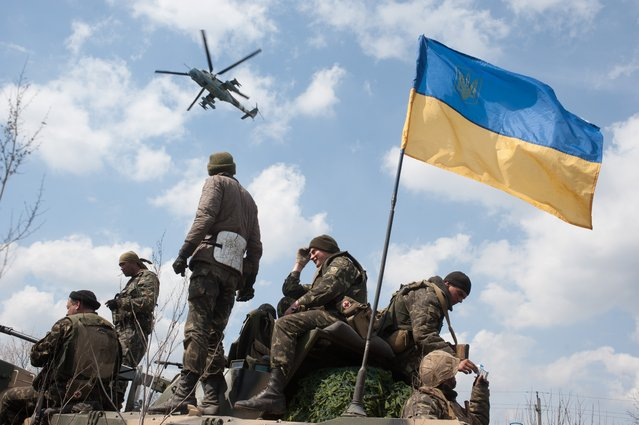 A military Ukrainian Army helicopter flies over a column of Ukrainian Army combat vehicles on the way to the town of Kramatorsk on Wednesday, April 16, 2014. (Photo by Evgeniy Maloletka/AP Photo)