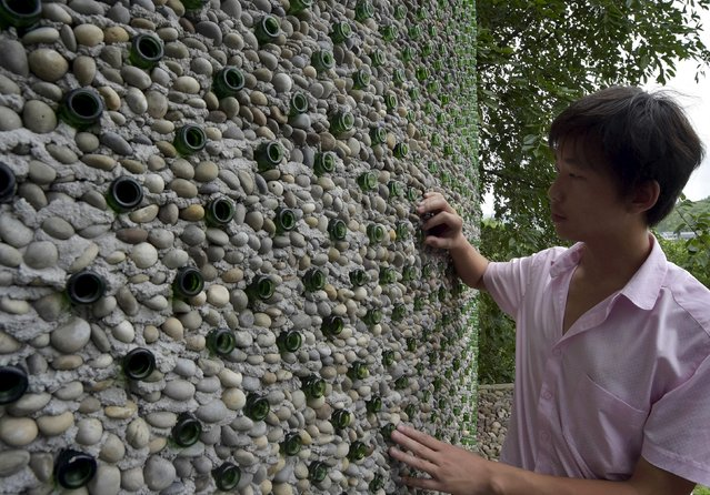 College graduate Li Rongjun looks at the exterior of a building made of 8,500 beer bottles, near his home in Lanya village of Chongqing municipality, China, June 26, 2015. (Photo by Reuters/Stringer)