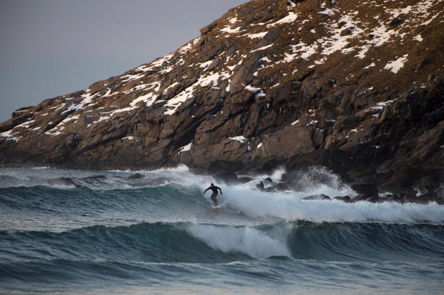 A surfer rides a wave in Unstad along the northern Atlantic Ocean on March 12, 2017, where the water temperatures is at five degrees centigrade and the air temperature is at minus two degrees centigrade. (Photo by Olivier Morin/AFP Photo)