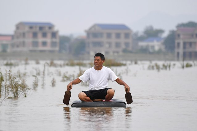 A villager sits on a stool inside a tyre as he rows himself on a flooded field along a river following heavy rainfall in Longtou village, Hengyang, Hunan province, China on July 10, 2019. (Photo by Yang Huafeng/CNS via Reuters)