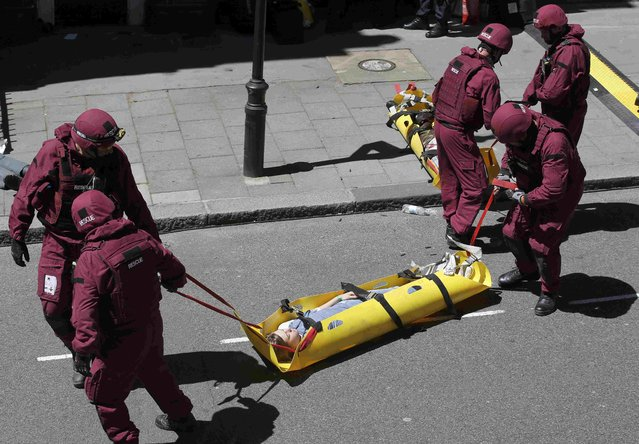 Member of the emergency services tend a casulty during Exercise Strong Tower at the scene of a mock terror attack at a disused underground station in central London, Britain June 30, 2015. (Photo by Peter Nicholls/Reuters)