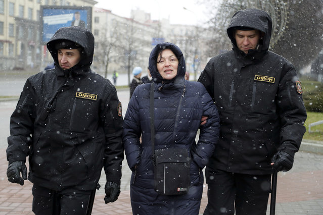 """Belarus police detain a woman prior to an opposition rally in Minsk, Belarus, Saturday, March 25, 2017. Police in Belarus cracked down hard Saturday on opposition protesters who tried to hold a forbidden demonstration in the capital – a human rights group said more than 400 people were arrested and many were beaten. The demonstrators had hoped to build on a rising wave of defiance of the former Soviet republic's authoritarian government, led by President Alexander Lukashenko, who has ruled since 1994. About 700 people had tried to march Saturday along Minsk's main avenue, but were blocked by a cordon of riot police wielding clubs and holding shields. After a standoff, the arrests began. """"They're beating the participants, dragging women by the hair to buses. I was able to run to a nearby courtyard"""", demonstrator Alexander Ponomarev said. Tatiana Revyako of the human rights group Vesna told The Associated Press that more than 400 people were arrested, saying """"many of the arrested were beaten and are in need of medical help"""". Police declined to comment on the arrests or the beatings. Among those arrested were about 20 journalists, according to the Belarusian Journalists' Association. In the days preceding Saturday's demonstration, more than 100 opposition supporters were sentenced to jail terms of three to 15 days, Vesna reported before the raid. Prominent opposition figure Vladimir Neklayev reportedly was pulled off a train by police overnight while trying to travel to Minsk. Belarus has seen an unusually persistent wave of protests over the past two months against Lukashenko, who recently claimed that a """"fifth column"""" of foreign-supported agitators was trying to bring him down. Saturday's demonstrators shouted slogans including """"Shame!"""" and """"Basta! (Enough!)"""" and deployed the red-and-white flag that is the opposition's symbol. The flag was first used by the short-lived independent Belarusian People's Republic in 1918 and again after the country's independence from th"""