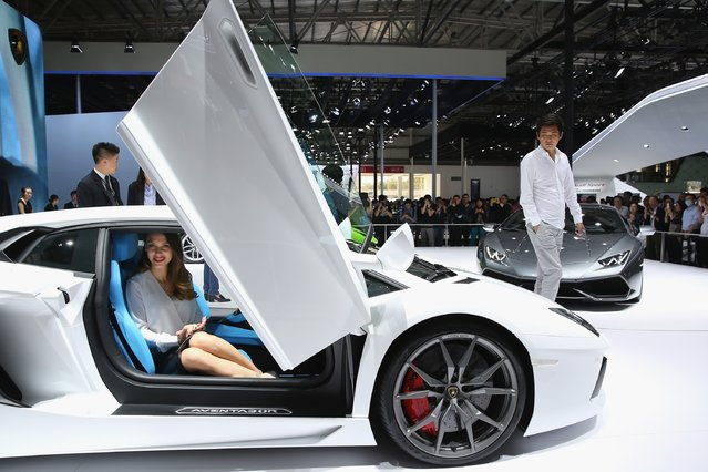 A model sits in a Lamborghini sport car as a potential consumer looks during the 2014 Beijing International Automotive Exhibition at China International Exhibition Center on April 21, 2014 in Beijing, China. (Photo by Feng Li/Getty Images)