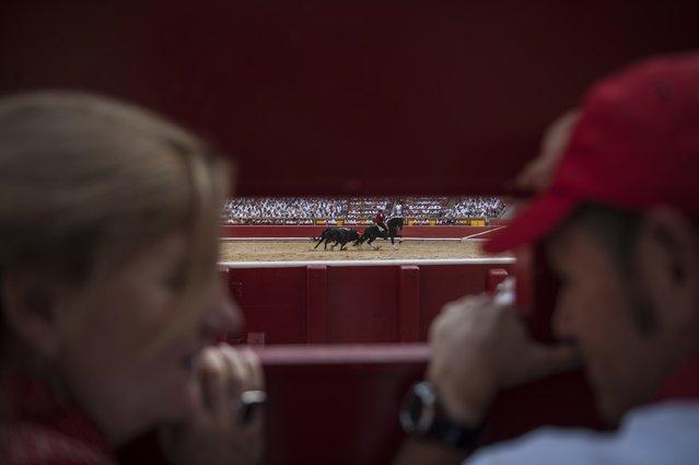 People watch Spanish mounted bullfighter Pablo Hermoso de Mendoza perform during a horseback bullfight at San Fermin Fiestas, in Pamplona, northern Spain, Monday, July 6, 2015. (Photo by Alvaro Barrientos/AP Photo)