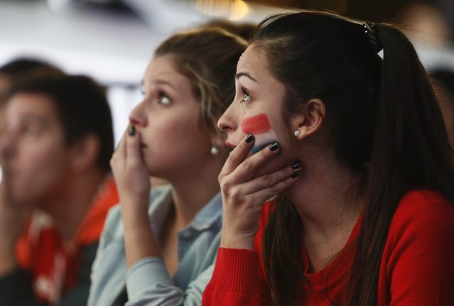 Fans of Paraguay's national soccer team watch the Copa America semifinal soccer match between Paraguay and Argentina, on a television screen in Asuncion, Paraguay, Tuesday, June 30, 2015. (Photo by Cesar Olmedo/AP Photo)