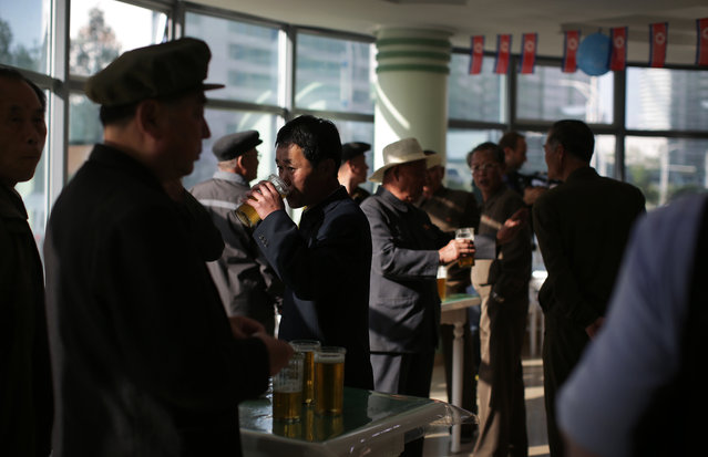 """In this Saturday, May 7, 2016, photo, North Korean men drink beer at the Taedonggang Beer shop in Pyongyang, North Korea. Ahead of the ongoing congress of North Korea's ruling Workers' Party, the nation was called upon to do massive overtime to boost production and show their devotion to leader Kim Jong Un in a 70-day """"loyalty campaign"""". And that's in addition to the hour after hour of rehearsals for huge rallies when their ruling party wraps up its first congress in decades. So how does a tired North Korean unwind? Beer. Beer. And more beer. (Photo by Wong Maye-E/AP Photo)"""