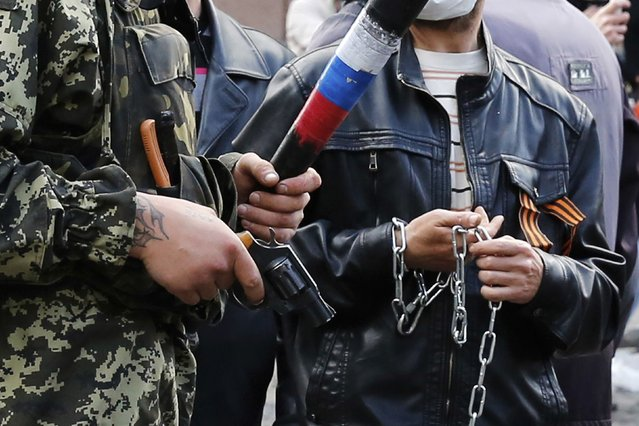 Armed pro-Russian activists look on during clashes with supporters of the Kiev government in the streets of Odessa May 2, 2014. (Photo by Yevgeny Volokin/Reuters)
