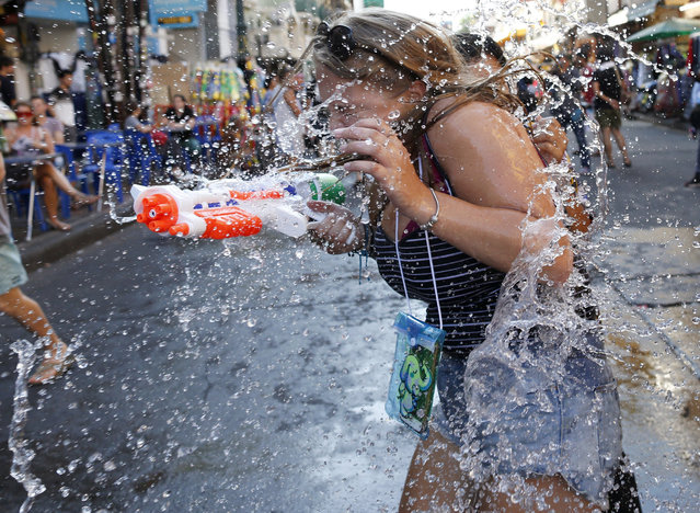 A Thai and foreign revelers battle with water guns during the annual Songkran celebration at Khaosan Road, a tourist spot in Bangkok, Thailand, 12 April 2017. (Photo by Rungroj Yongrit/EPA)