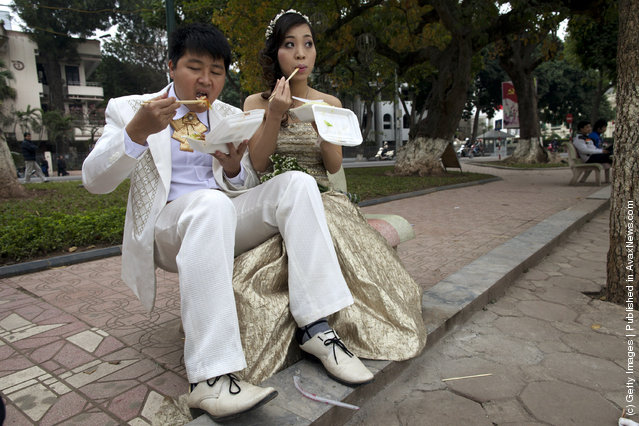 A wedding couple poses for a photographer during a wedding photo shoot