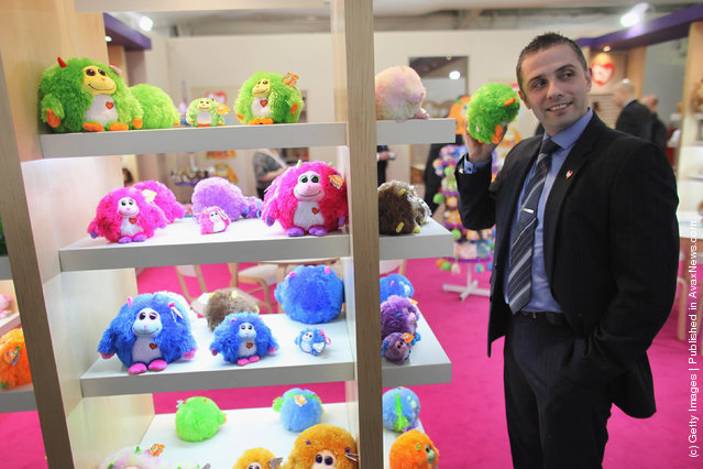 A sales representative listens to the noises made by a 'Monstaz' toy on display at  the 2012 London Toy Fair