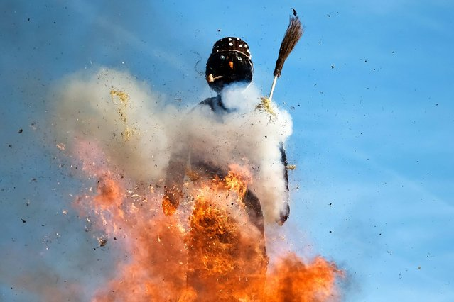 The Boeoegg, a giant symbolic snowman made of wadding and and filled with firecrackers burns on top of a bonfire in Sechselaeuten square on April 24, 2017 in Zurich. When the bells of the Saint Peter's church chime six o'clock, the bonfire under the snowman is set in fire and the guildsmen wearing historical costumes ride around the bonfire. The faster the head of the snowman explods the warmer and more beautiful the summer will be. (Photo by Michael Buholzer/AFP Photo)